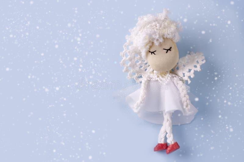 Weihnachtskartenplan mit handgemachtem Engel in der weißen Kleidung auf einem schneebedeckten hellblauen Hintergrund Kopieren Sie stockfoto