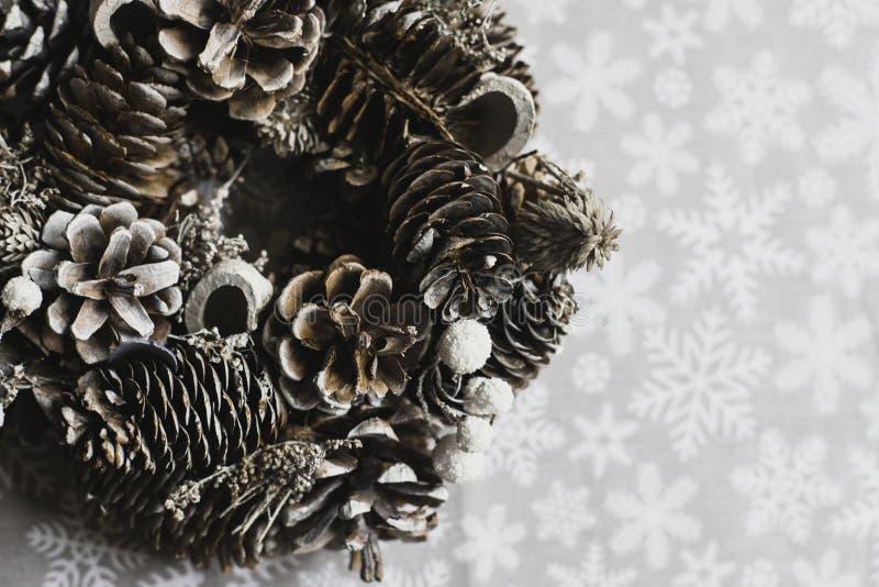 Weihnachtskegel winden auf Schneeflockenhintergrund natürliche Weihnachtsdekorationen lizenzfreies stockbild