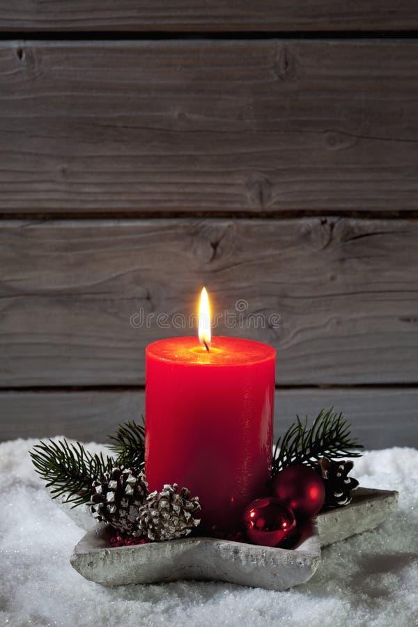 Weihnachtskerze im Kerzenhalter auf Haufen des Schnees gegen hölzernen Hintergrund stockfotografie