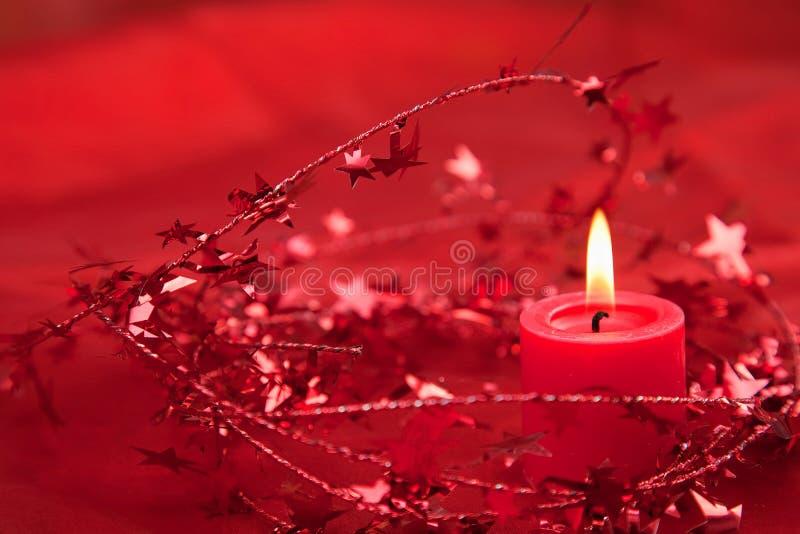 Weihnachtskerze mit Dekoration im Rot stockfotos