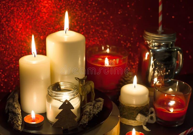 Weihnachtskerzen und Feiertagsdekorationen auf rotem unscharfem abstraktem Hintergrund stockfotografie