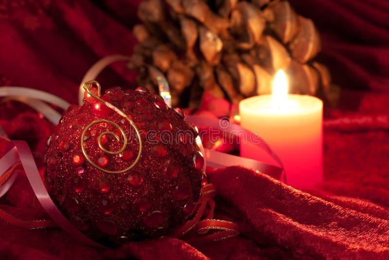 Weihnachtskerzen und -flitter auf Rot lizenzfreie stockfotos
