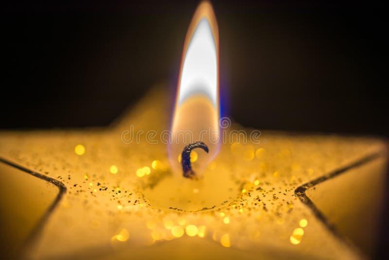 Weihnachtskerzenlicht einer sternf?rmigen Kerze vor einem dunklen Hintergrund stockfoto