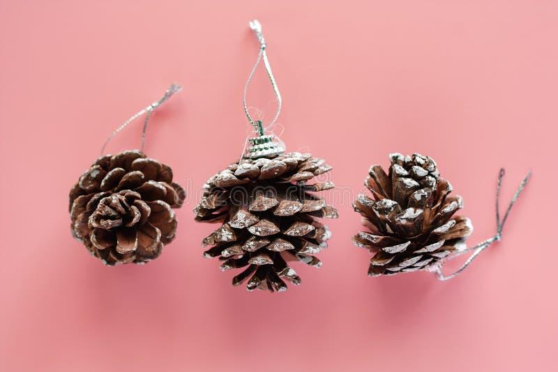 Weihnachtskiefernkegelverzierungen und -dekoration auf rosa Hintergrund lizenzfreie stockbilder