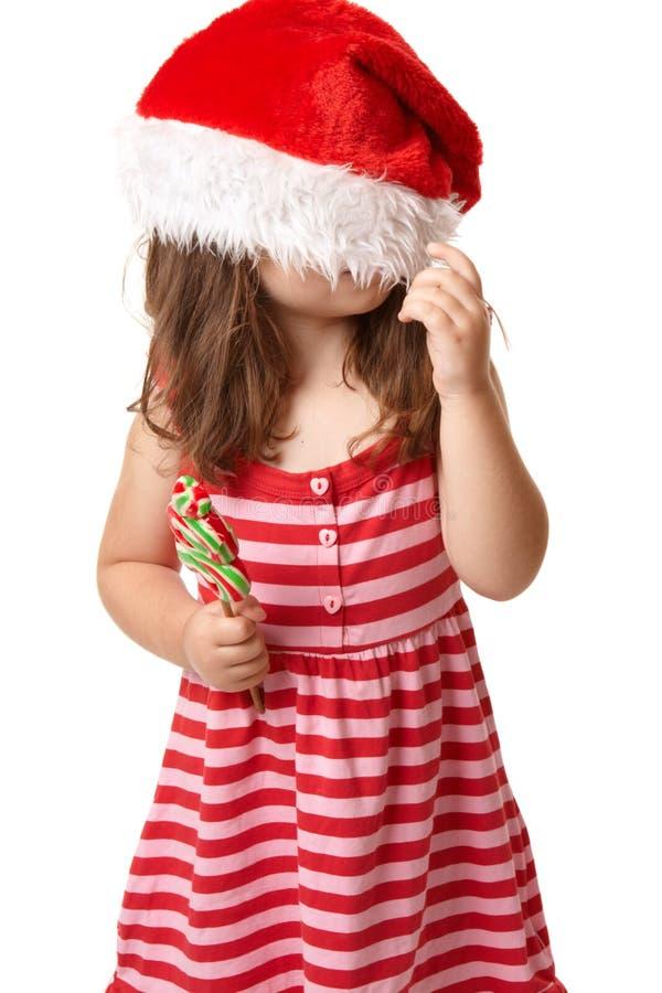 Weihnachtskind mit Sankt-Hut lizenzfreie stockbilder