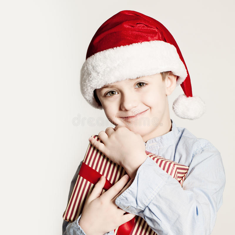 Weihnachtskind mit Weihnachtsgeschenkbox Kinderjunge mit roter Santa Hat lizenzfreies stockbild