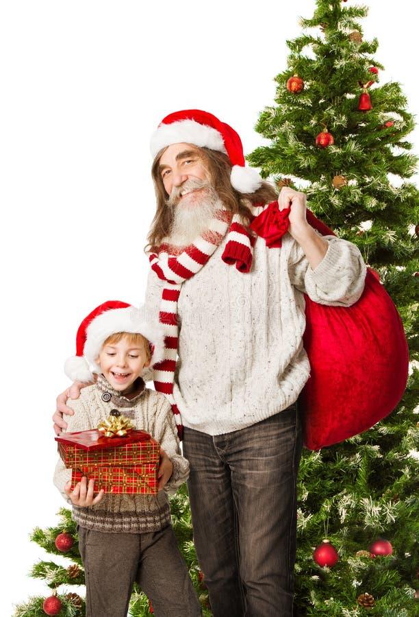 Weihnachtskind stellt sich, großväterliche haltene Tasche Santa Clauss dar lizenzfreies stockfoto