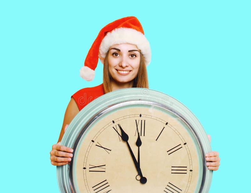 Weihnachtskonzept - glückliche lächelnde Frau in rotem Hut Sankt, der das Zeigen der großen Uhr hält stockfotos
