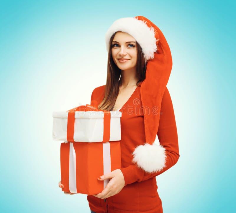 Weihnachtskonzept - glückliche lächelnde junge Frau in rotem Hut Sankt mit Kastengeschenken lizenzfreie stockfotos