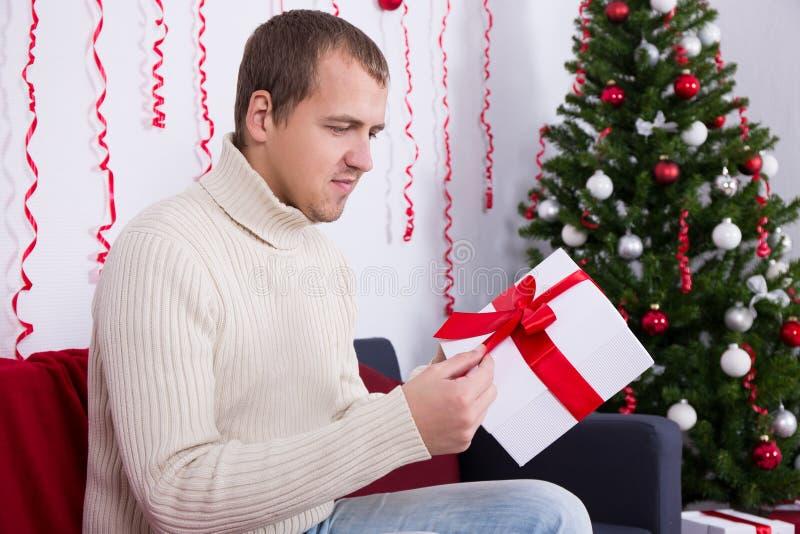 Weihnachtskonzept - glückliches junges Öffnungsgeschenk des gutaussehenden Mannes im liv lizenzfreie stockbilder