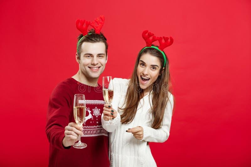 Weihnachtskonzept - glückliches junges Paar in den Strickjacken, die Weihnachten mit Champagne feiern lizenzfreies stockfoto