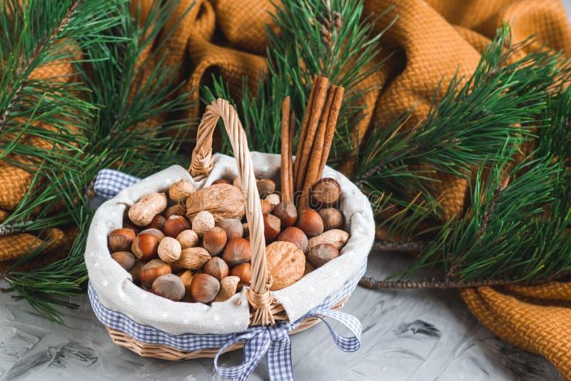 Weihnachtskonzept-Korb mit sortiertem Mischnuss-Erdnuss-Mandel-Haselnuss-Kiefern-Niederlassungs-gelbe Decken-gemütlichem gesundem stockfotos