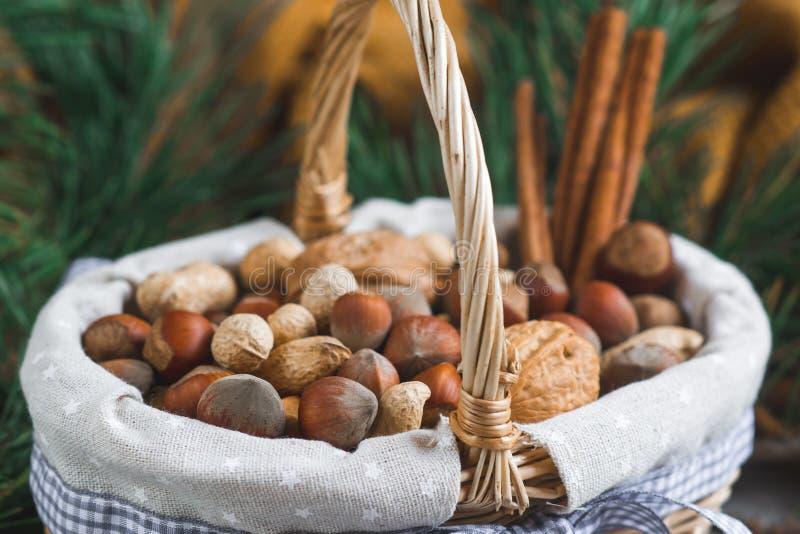 Weihnachtskonzept-Korb mit sortiertem Mischnuss-Erdnuss-Mandel-Haselnuss-Kiefern-Niederlassungs-gelbe Decken-gemütlichem gesundem stockbilder