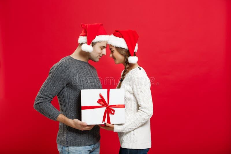 Weihnachtskonzept - lokalisiertes reizendes junges Paar, das fest mit weißem Geschenk über rotem Hintergrund hält lizenzfreies stockbild