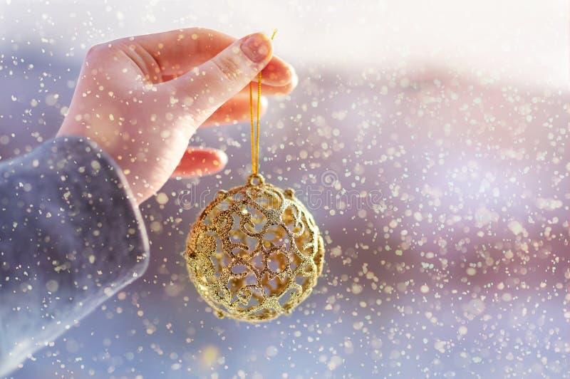 Weihnachtskonzept mit der Hand und goldenem Ball - Weihnachtsbaumspielzeug Weihnachtsdekoration auf Schneehintergrund stockbilder