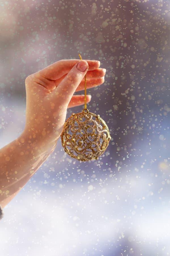 Weihnachtskonzept mit der Hand und goldenem Ball - Weihnachtsbaumspielzeug Weihnachtsdekoration auf Schneehintergrund stockfoto