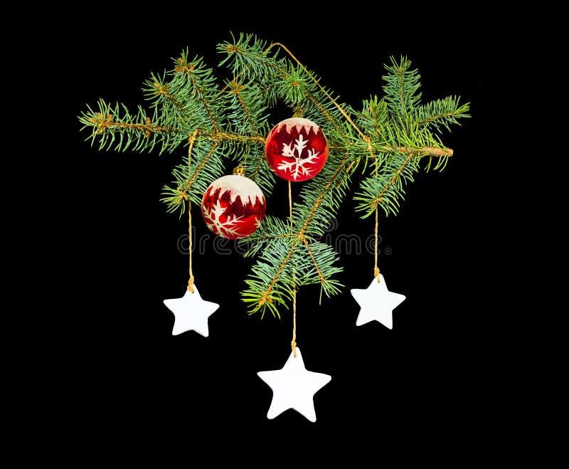 Weihnachtskonzept mit grüner Niederlassung, rote Bälle, Sterne, schwarzer Hintergrund stock abbildung