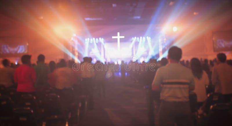 Weihnachtskonzept: Unscharfer Christian Congregation Worship God zusammen in der Kirchenhalle vor Musikstadium und in Lichteffekt lizenzfreie stockfotografie