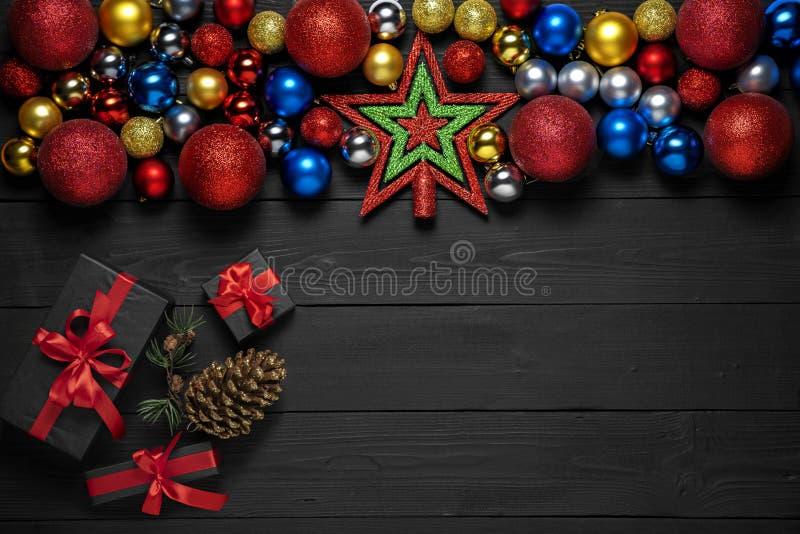 Weihnachtskonzeptdekoration mit Neujahrsgeschenkkästen mit rotem Band, Tannenzweige, Kiefernkegel auf schwarzem hölzernem Hinterg lizenzfreie stockfotografie