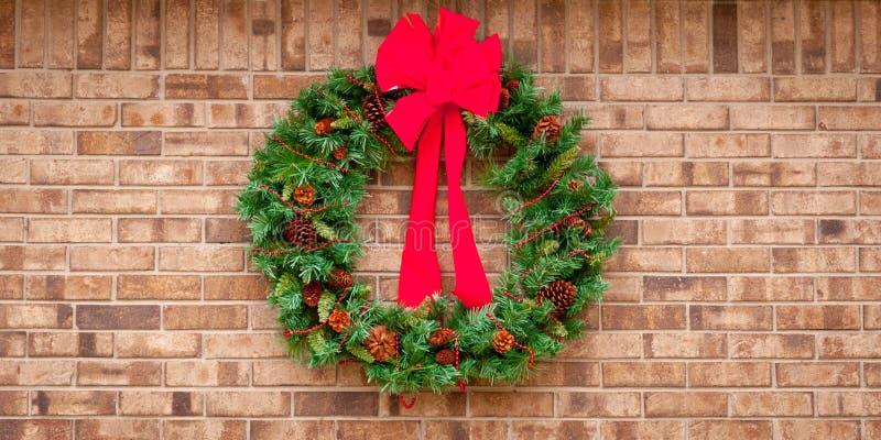 WeihnachtsKranz, der an einer Backsteinmauer mit Exemplarplatz hängt stockfotografie