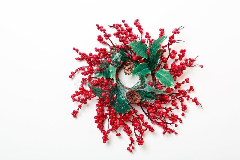 Weihnachtskranz von den Stechpalmenbeeren und -immergrün lokalisiert auf weißem Hintergrund stockbild