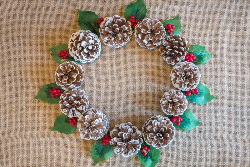 Weihnachtskranz von pinecones, von Stechpalmenblättern und von roten Beeren auf rustikalem Gewebehintergrund lizenzfreie stockbilder