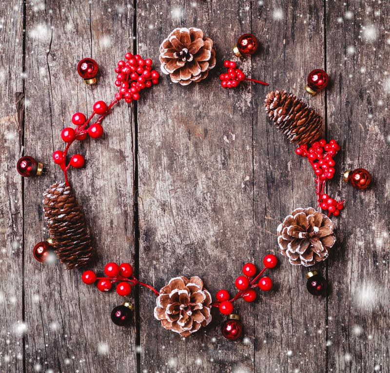 Weihnachtskranz von Tannenzweigen, Kegel, rote Dekorationen auf dunklem hölzernem Hintergrund stockbild
