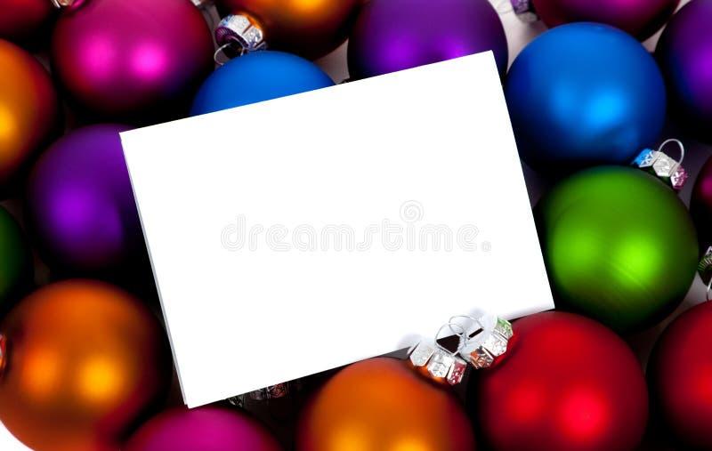 Weihnachtskugeln/Flitter mit einem notecard auf Weiß lizenzfreie stockbilder