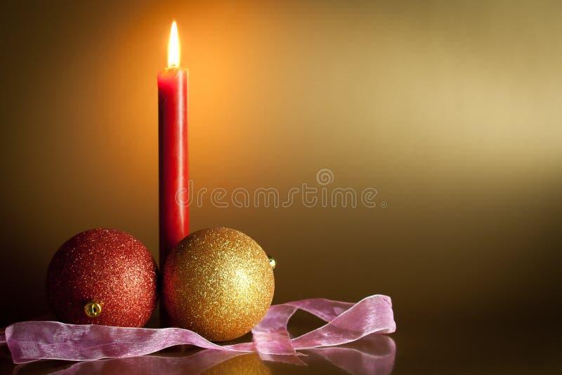 Weihnachtskugeln mit roter Kerze im Hintergrund lizenzfreie stockfotos