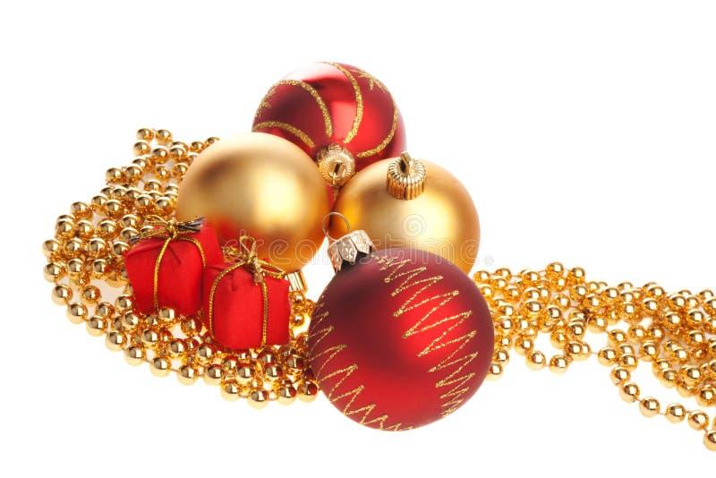 Weihnachtskugeln und anwesende Kästen, die auf Kornen liegen lizenzfreie stockfotos