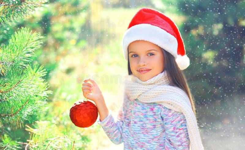 Weihnachtslächelndes Kinderkleines Mädchen in rotem Hut Sankt mit Ball nahe Niederlassungsbaum stockfoto