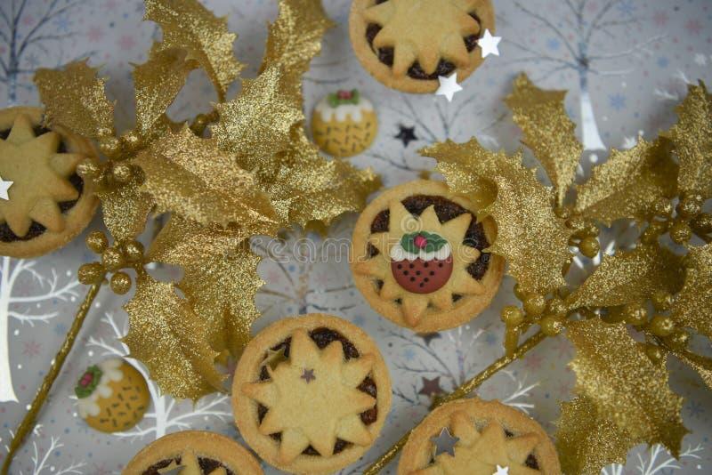 Weihnachtslebensmittel-Fotografiebild mit Saisongebäck zerkleinern Torten und Goldfunkeln bedeckte Stechpalme mit Puddingdekorati lizenzfreie stockbilder