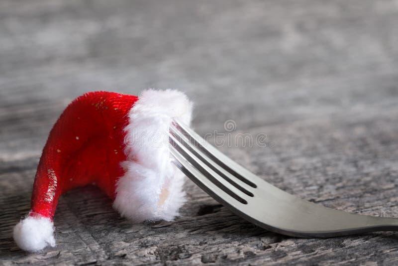 Weihnachtslebensmittelmenü-Zusammenfassungshintergrund mit Gabel und Weihnachtsmann-Hut auf Tabelle stockfotografie