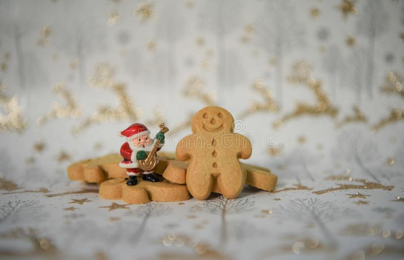 Weihnachtslebensmittelphotographie-Lebkuchenmann-Minimusik Weihnachtsmann auf Goldrenfunkelnweihnachtspackpapierhintergrund stockfotografie