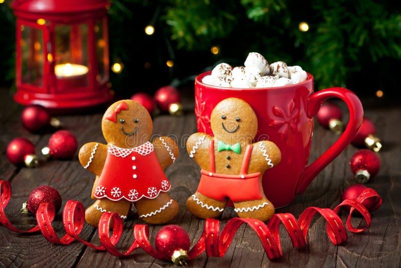 Weihnachtslebkuchenplätzchen, Feiertagsdekoration und heiße Schokolade im Becher auf hölzernem Hintergrund stockfotografie