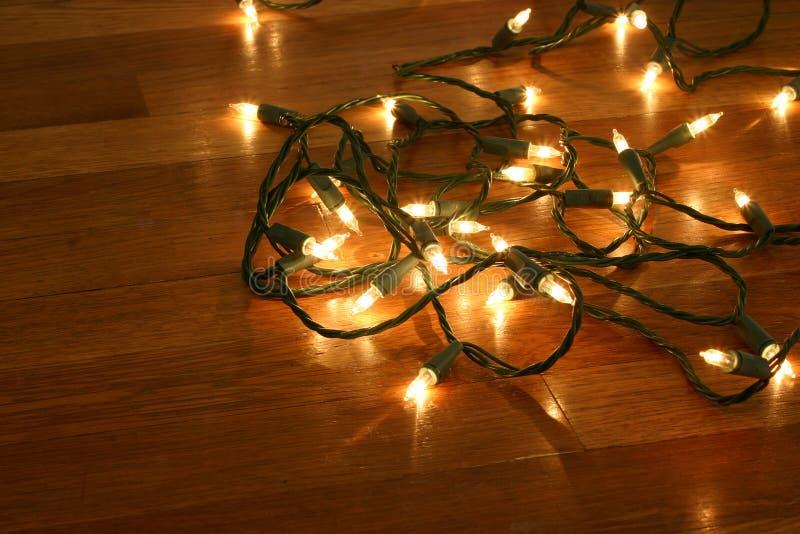 Weihnachtsleuchten auf hölzernem Fußboden lizenzfreie stockbilder