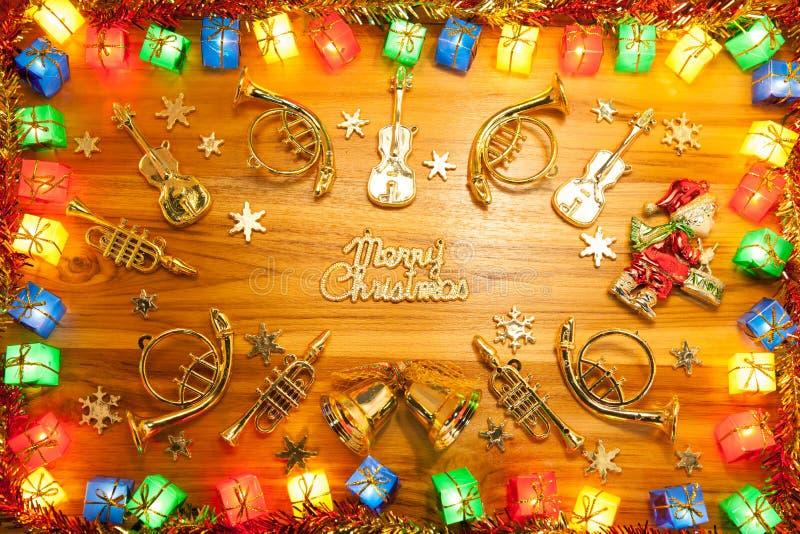 Weihnachtslicht-Geschenkboxrahmen und Musikinstrument auf Goldenem lizenzfreie stockfotografie