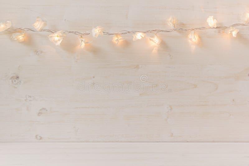 Weihnachtslichter, die auf einem weißen hölzernen Hintergrund brennen lizenzfreie stockbilder