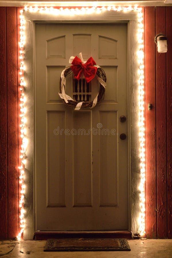 Weihnachtslichter und -Kranz auf Haustür nachts lizenzfreies stockbild