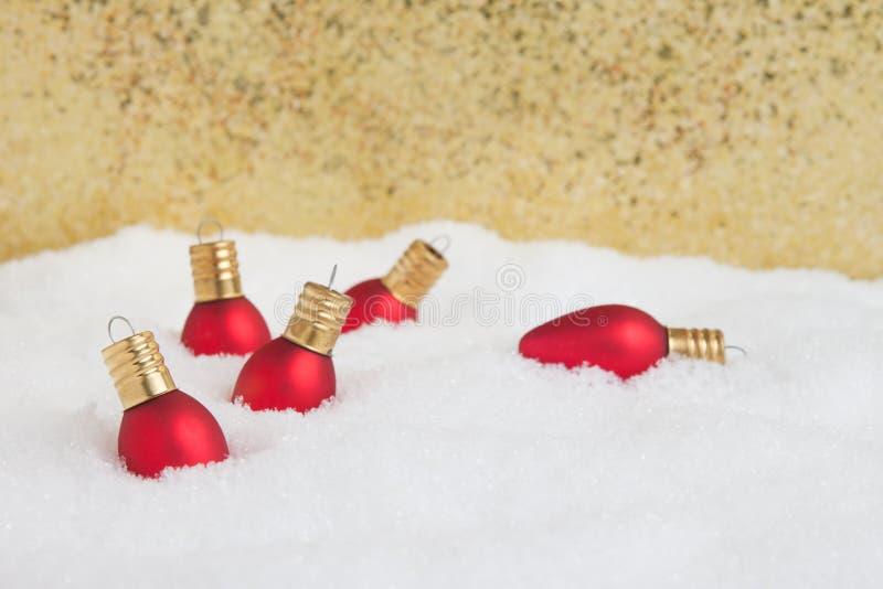 Weihnachtslichtverzierungen im Schnee mit Goldhintergrund stockfotografie