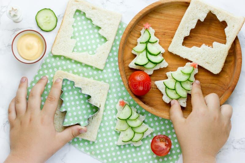 Weihnachtslustige Sandwiche mit Gurkenscheibe, Tomatenstern und lizenzfreies stockbild