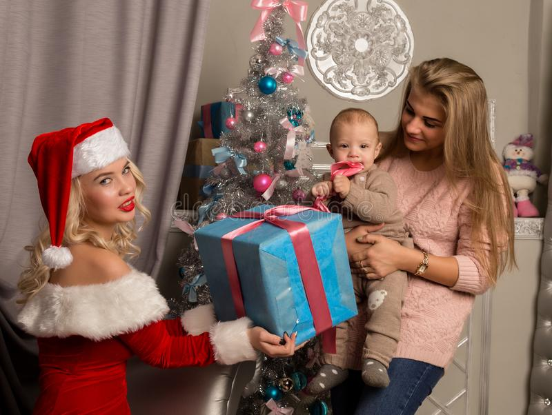 Weihnachtsmädchen, das dem kleinen Baby Geschenke gibt Frau gekleidet als Weihnachtsmann stockfoto
