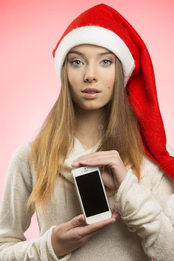 Weihnachtsmädchen mit Smartphone stockfotografie