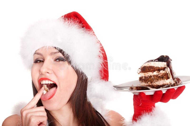 Weihnachtsmädchen in Sankt-Hut essen Kuchen. stockfotos