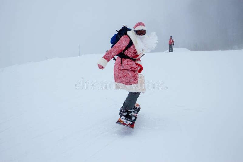Weihnachtsmann auf einem Snowboard lizenzfreie stockfotos