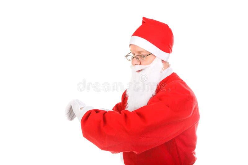 Weihnachtsmann-Blick auf Uhr lizenzfreie stockbilder