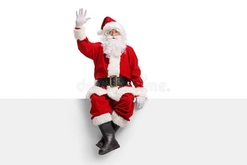 Weihnachtsmann, der auf einer Platte und einem Wellenartig bewegen sitzt stockbilder