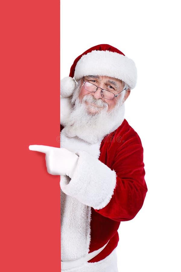 Weihnachtsmann, der auf unbelegte Fahne zeigt stockfoto