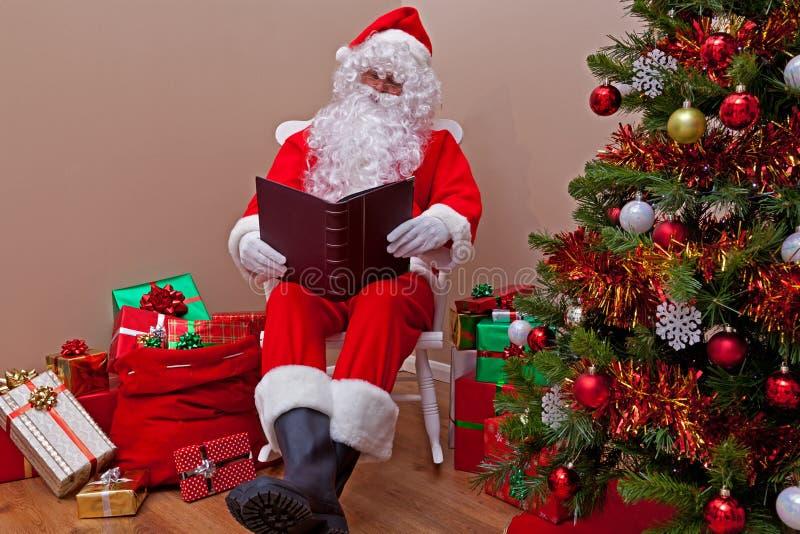 Weihnachtsmann, der die Liste liest stockfotos