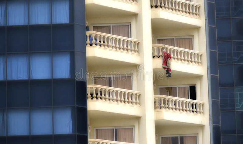 Weihnachtsmann, der ein Gebäude im Weihnachten steigt lizenzfreie stockbilder